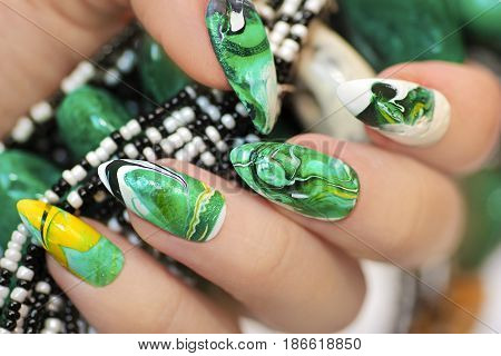 Stone nail design in white and green colors with veins of dark and yellow color nail Polish on a sharply oval-shaped nails closeup.