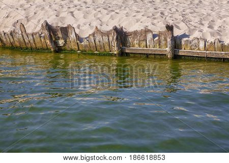 wooden pier in the sea and sandy beach