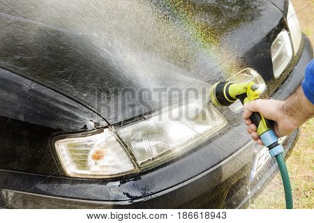 Washing the car. Man rinses the car's mask holding the garden hose.