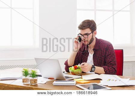 Busy at work, overworking. Man has business lunch in office, talking on mobile and reading papers.