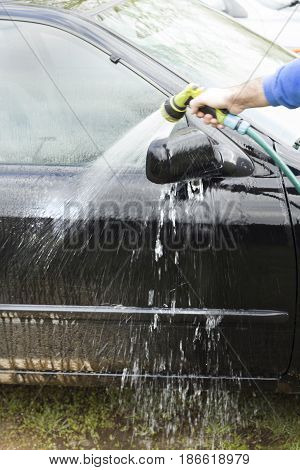 Washing car door. Man rinses dirt out of a door with a stream of water from a garden hose.
