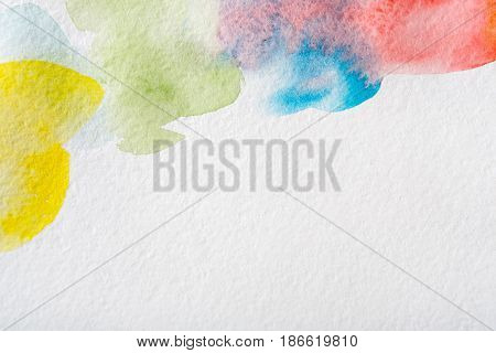 Abstract watercolor spots painted texture background. Red, violet and blue on white with copy space