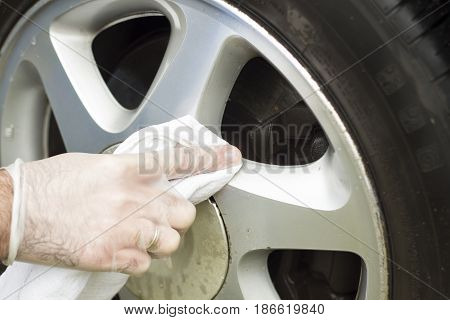 The male hand wipes the aluminum rim with a white cloth.