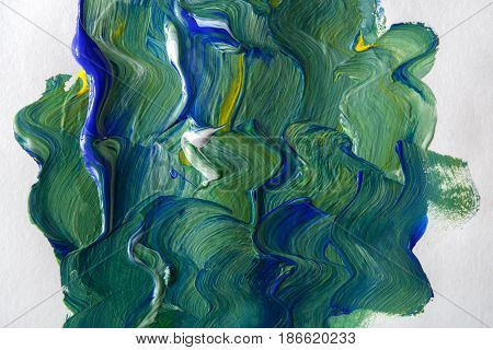 Palette with green and white mixed oil-paints texture on canvas, close-up, abstract background