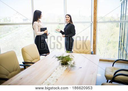 Two Beauty Businesswomen Having Informal Meeting In Modern Office