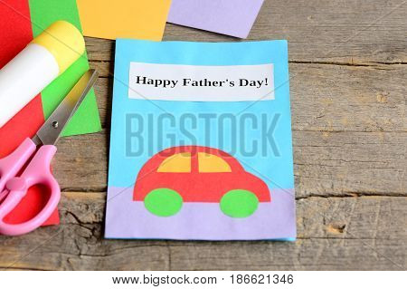 Father's day card. Colored paper sheets, scissors, glue stick on vintage wooden background. Cute Father's day greeting card children can make for daddy. Simple paper craft for children to do. Closeup