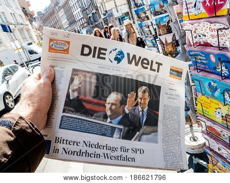 PARIS FRANCE - MAY 15 2017: Man buys German Die Welt newspaper reporting handover ceremony presidential inauguration of the newly elected French President Emmanuel Macron in Paris France