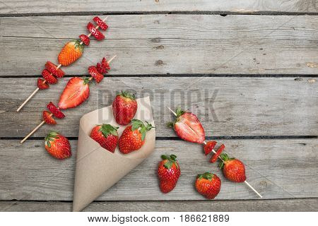 Whole Fresh Red Strawberries Scattered Of Paper Cone And Sliced Strawberries On Wooden Skewers, Berr