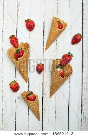 Fresh Red Strawberries Scattered Of Waffle Cones On White Wooden Tabletop, Berries On Wood Concept