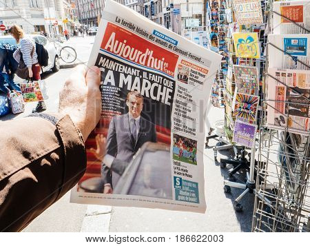PARIS FRANCE - MAY 15 2017: Man buys Aujord'hui French newspaper reporting handover ceremony presidential inauguration of the newly elected French President Emmanuel Macron in Paris France