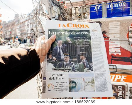 PARIS FRANCE - MAY 15 2017: Man buys La Croix French newspaper reporting handover ceremony presidential inauguration of the newly elected French President Emmanuel Macron in Paris France