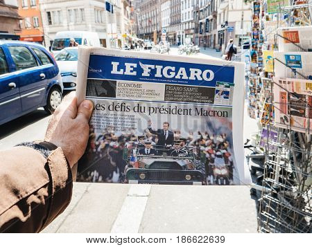 PARIS FRANCE - MAY 15 2017: POV over Le Figaro an buys newspaper reporting handover ceremony presidential inauguration of the newly elected French President Emmanuel Macron in Paris France