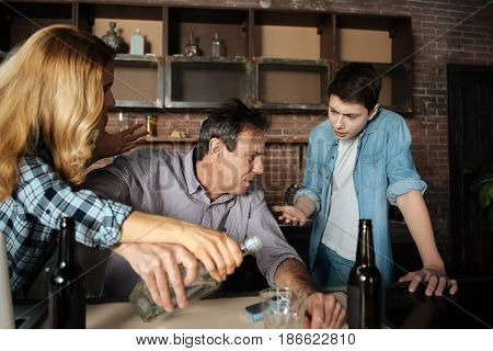 You surprised us. Angry man holding bottle with vodka in right hand wrinkling forehead while turning head to his son