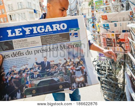 PARIS FRANCE - MAY 15 2017: Le Figaro newspaper with black ethnicity man buying newspaper reporting handover ceremony presidential inauguration of the newly elected French President Emmanuel Macron in Paris France