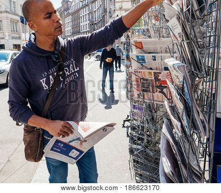 PARIS FRANCE - MAY 15 2017: Black ethnicity man buys international newspaper reporting handover ceremony presidential inauguration of the newly elected French President Emmanuel Macron in Paris France