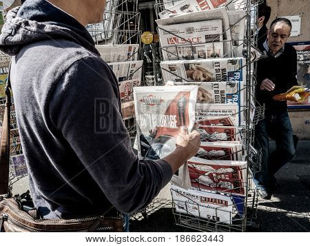 PARIS FRANCE - MAY 15 2017: Man buys Liberation with Good Luck mesage to Macron - newspaper reporting handover ceremony presidential inauguration of the newly elected French President Emmanuel Macron in Paris France