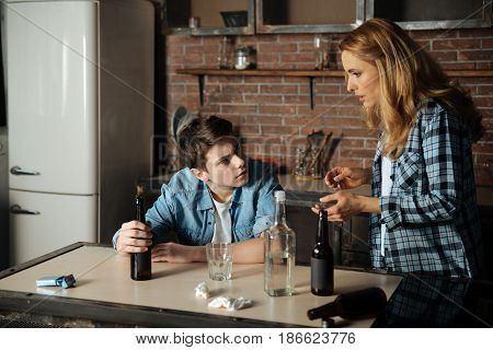 Put it away. Angry teenager wrinkling his forehead holding bottle in right hand while looking at his mother