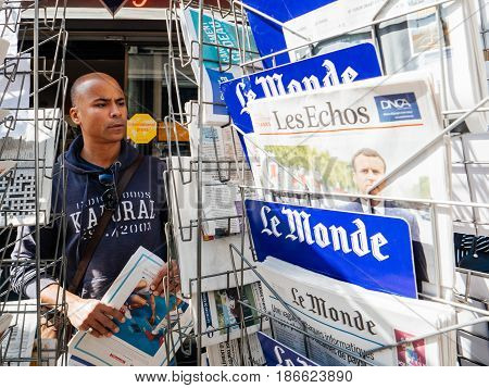PARIS FRANCE - MAY 15 2017: Black ethnicity man buying Le monde newspaper reporting handover ceremony presidential inauguration of the newly elected French President Emmanuel Macron in Paris France