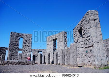 Tourist examines a pillar at the Maryhill Stonehenge at Maryhill, Washington