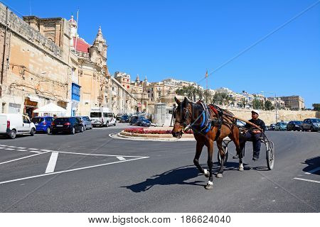 VALLETTA, MALTA - MARCH 30, 2017 - Man riding a horse and trap past a traffic island with Victoria Gate Ta Liesse Church and town buildings to the rear Valletta Malta Europe, March 30, 2017.