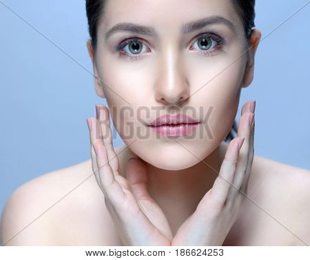 beauty closeup portrait of attractive young  caucasian woman brunette on blue background studio shot lips face skin care applying cream.