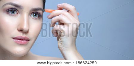 Beauty Woman with Perfect skin. Young Caucasian with Fresh looking Skin.Face Closeup. Plucking Eyebrows with Tweezers.