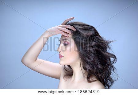 closeup beauty portrait of attractive young caucasian woman brunette on blue background  studio shot lips face hair