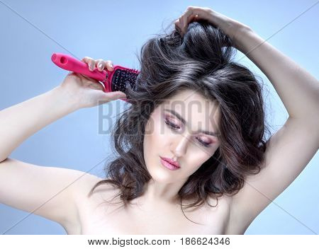 beauty closeup portrait of attractive young  caucasian woman brunette on blue background studio shot lips face skin care hands. Combing her hair