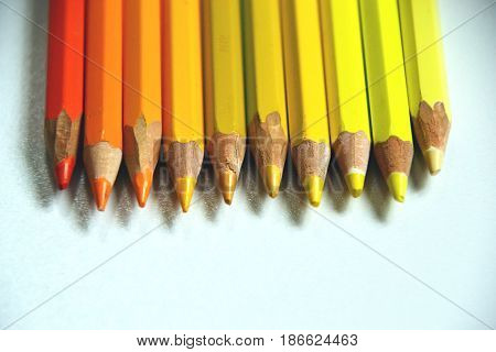 Yellow and orange pencils lie in a row