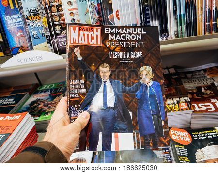 PARIS FRANCE - MAY 15 2017: Man buys Paris Match magazine with Emmanuel Macron and his wife Brigitte Trogneux during handover ceremony presidential inauguration of the newly elected French President Emmanuel Macron in Paris France