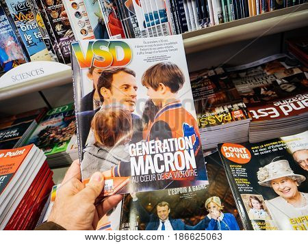 PARIS FRANCE - MAY 15 2017: Man buys VSD magazine with Macron Generation on cover French President Emmanuel Macron in Paris France