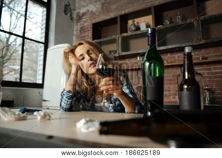 Drink for female. Enigmatical woman wearing checked shirt touching her head while examining glass