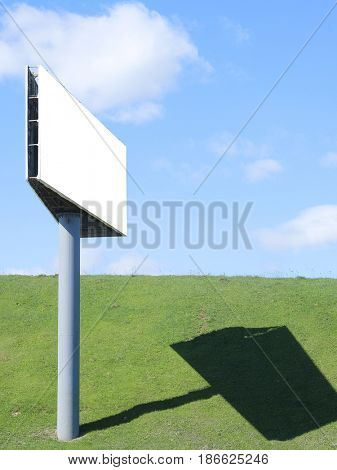 Billboard against the background of a green meadow and the sky