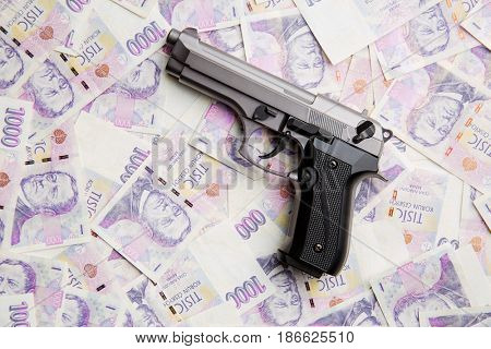 Handgun and czech paper money.  Top view.