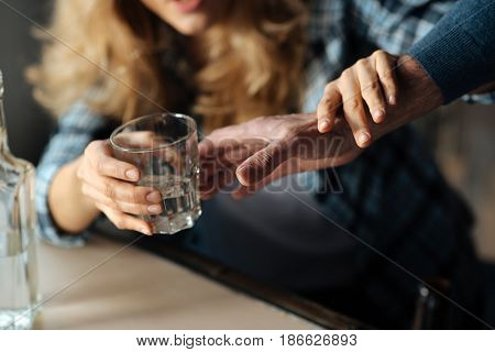 Everything is okay. Strong male hand stretching to take glass and drunk female touching it
