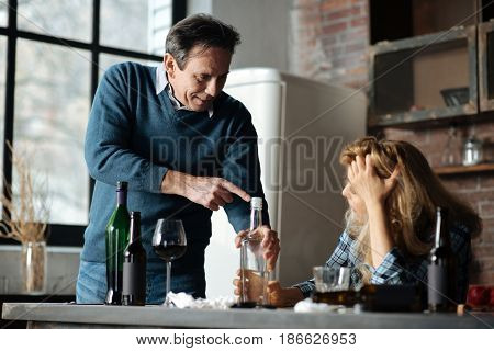 Do not take this. Smiling male person holding bottle in left hand bowing his head while standing opposite his wife while