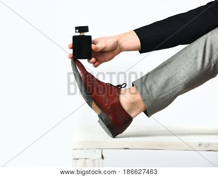 Strong Male Leg And Hand Holding Perfume On Wooden Bench
