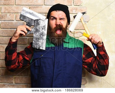 bearded painter man long beard brutal caucasian hipster with moustache in uniform holding various building tools hammer roller paint and spatulas with satisfied face on brick wall studio background
