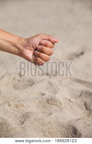 Sand running through female hands.Young woman with sand in her hands. Sand as