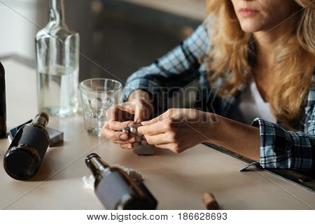 Take pills. Sad woman wearing checked shirt leaning arms on table while going to eat all tablets