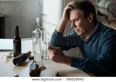 Thoughtful mood. Serious man touching his head wrinkling forehead while looking at tablets