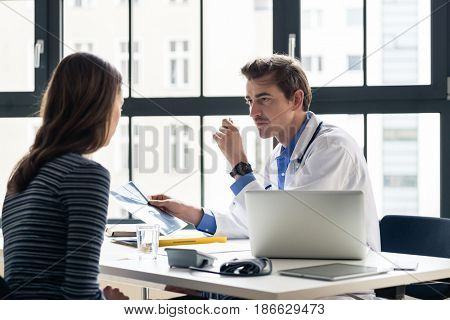 Young devoted doctor holding an X-ray while listening with attention to his female patient during a private consultation in the office poster