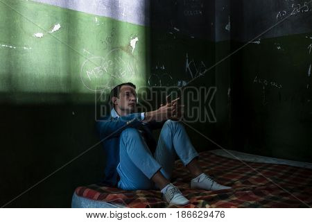 Depressed young man thinking and waiting while sitting on a dirty mattress in a dark obsolete prison cell during custody