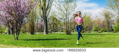 Woman running for better fitness though a park in spring