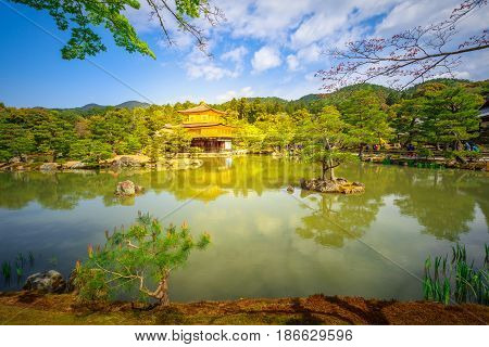 Scenic landmark Kinkakuji or Rokuonji, Unesco site of Kyoto, reflected on lake.The Golden Pavilion, whose top two floors are completely covered in gold leaf, is a ancient Zen temple. Day light shot.