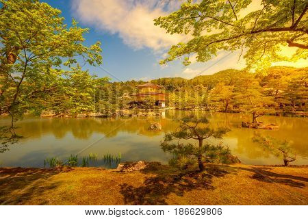Colorful Kinkaku-ji, Golden Pavilion, famous buddhist temple zen in Kyoto reflected in the lake. The Rokuonji is one of most visited Kyoto temples. Shot at sunset. Concept of Buddhism and meditation.