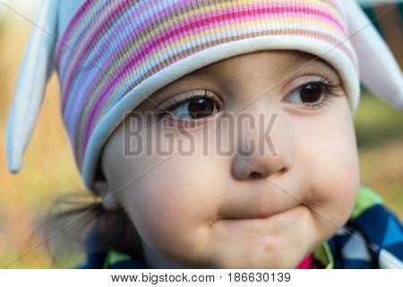Child girl portrait. On the head wearing a hat.