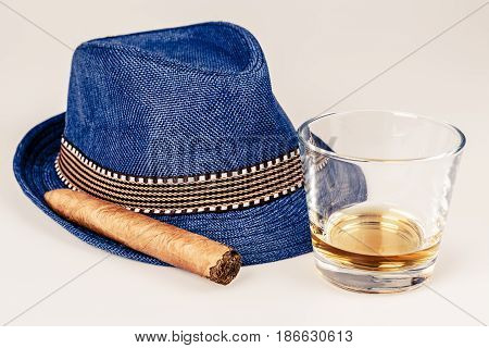 blue hat with cigar and expensive drink of whisky or rum on white floor. Gentleman or hipster relax concept