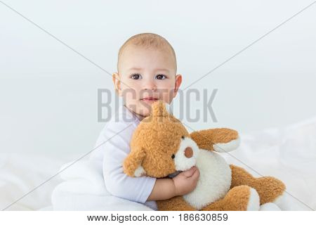 Portrait Of Adorable Small Baby Boy With Teddy Bear Playing On Bed, 1 Year Old Baby Concept