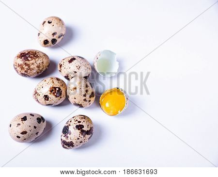 Fresh quail eggs in the shell one egg is broken white surface empty space on the right